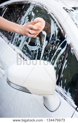 Man Washing White Car With Sponge