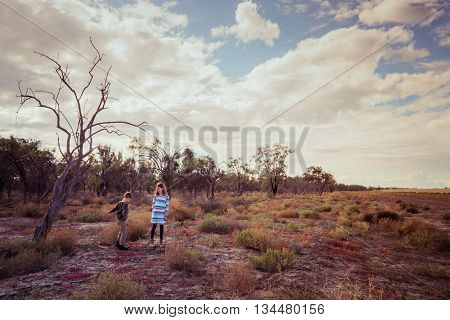 Brother and sister standing beside an old tree in outback Australia