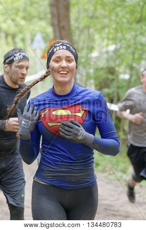 STOCKHOLM SWEDEN - MAY 14 2016: Smiling woman dressed as Superman with braids running in the forest in the obstacle race Tough Viking Event in Sweden May 14 2016