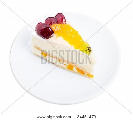Creamy yougurt mousse cake with fruits on top. Isolated on a white background.