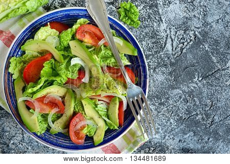 Salad with avocado tomato romaine lettuce and olive oil dressing with space for text