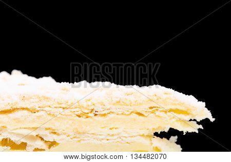 Russian Napoleon cake. Macro. Against black background.