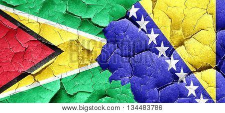 Guyana flag with Bosnia and Herzegovina flag on a grunge cracked