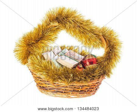 Wicker basket full of euro bills with christmas golden tinsel and bright Christmas balls. Isolated on a white background.