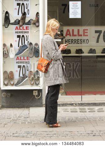 COPENHAGEN DENMARK - CIRCA JUNE 2016: unidentified blonde fashion girl checking her mobile phone on the street