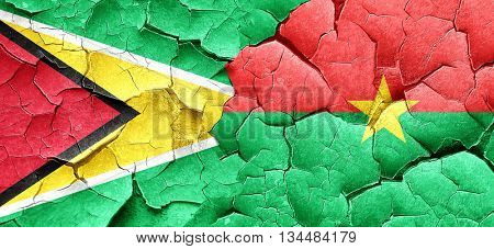 Guyana flag with Burkina Faso flag on a grunge cracked wall