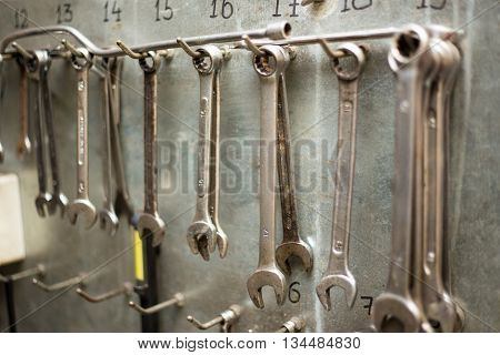 set of old wrenches and spanners on metal wall
