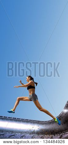Profile view of sportswoman jumping against composite image of a stadium