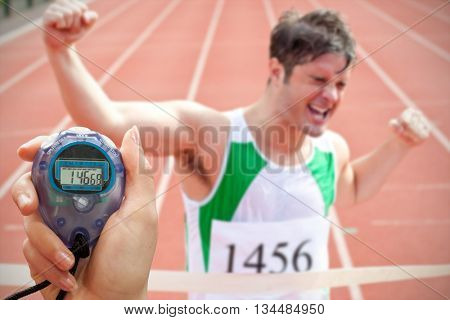 Close up of a hand holding a timer against exulting sprinter showing expression of victory in front of the arrival line