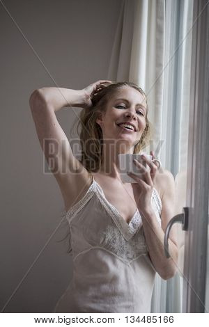 Attractive woman drinking coffee by the window in her night gown