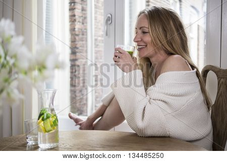 Attractive blonde drinking a green smoothie in the morning