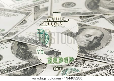 Dollar sign carved out of hundred dollar bills on money background