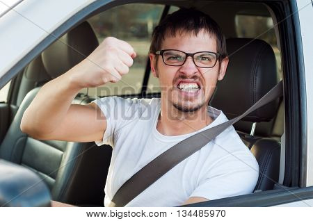Male caucasian angry driver is showing his fist and mad face