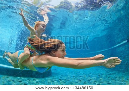 Happy family - mother baby girl learn to swim and dive underwater with fun in pool. Healthy lifestyle active parents people water sports activity and swimming lessons on summer holidays with child