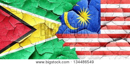 Guyana flag with Malaysia flag on a grunge cracked wall