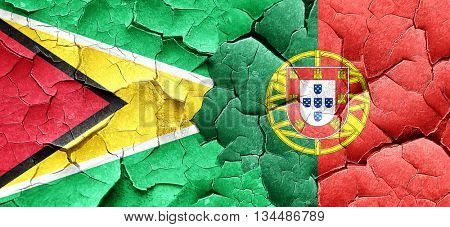 Guyana flag with Portugal flag on a grunge cracked wall