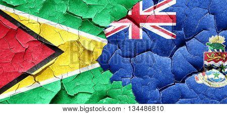 Guyana flag with Cayman islands flag on a grunge cracked wall