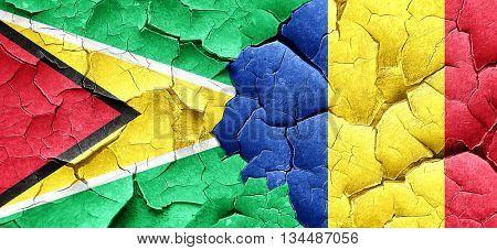 Guyana flag with Romania flag on a grunge cracked wall