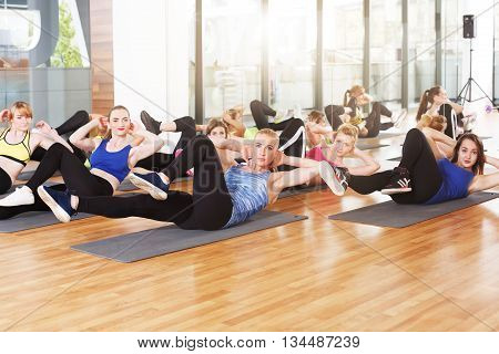 Group of young women in fitness class. Group of people making exercises. Girls do cross crunches for abs. Healthy lifestyle, training, sport, gym studio. Sporty girls in fitness club, aerobics.