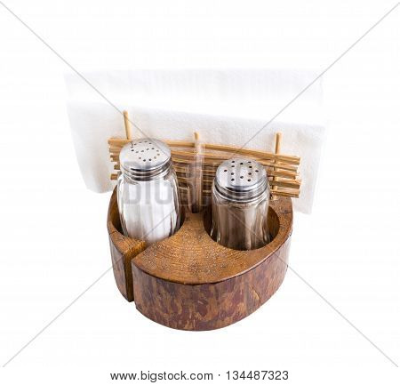 Pepper and salt shakers with napkin holder in rustic style on wooden board. Isolated on a white background.