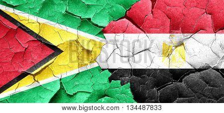 Guyana flag with egypt flag on a grunge cracked wall
