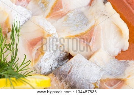 Sliced herring and dill on plate. Part of fish platter closeup. Macro. Photo can be used as a whole background.