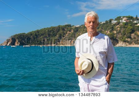 Man in white suit at the beach looking at the sea