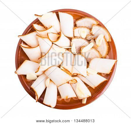 Sliced pork fat lard. Delicious ukrainian starter. Served on brown clay plate. Isolated on a white background.