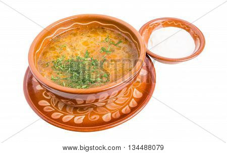 Traditional chicken soup with fresh green and sour cream. Isolated on a white background.