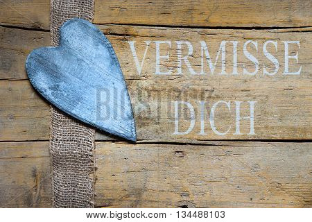 Jute Ribbon And Heart On Wooden Table, German Text, Concept Miss You