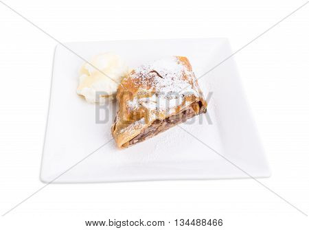 Delicious strudel with apple and walnuts. Served with scoop of vanilla ice cream. Isolated on a white background.