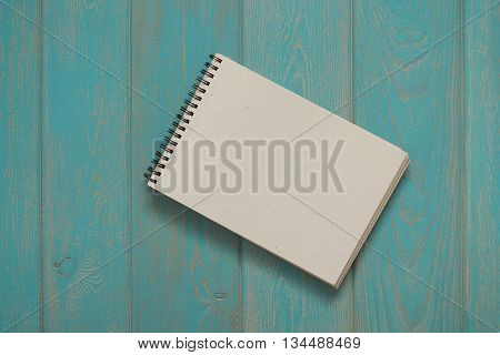 Note book on blue wooden desk. Top view.