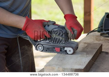 Man Grinds A Board With Sander