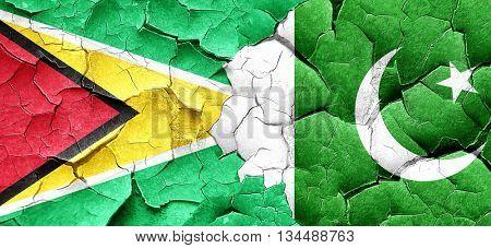 Guyana flag with Pakistan flag on a grunge cracked wall