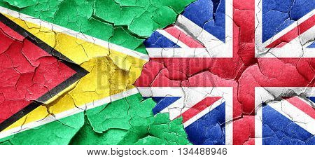 Guyana flag with Great Britain flag on a grunge cracked wall