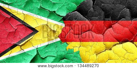 Guyana flag with Germany flag on a grunge cracked wall