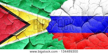 Guyana flag with Russia flag on a grunge cracked wall