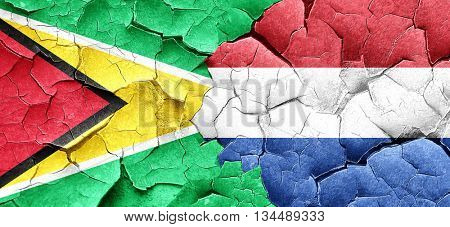 Guyana flag with Netherlands flag on a grunge cracked wall