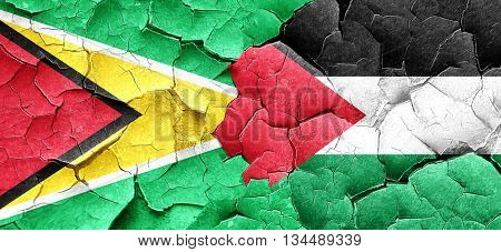 Guyana flag with Palestine flag on a grunge cracked wall