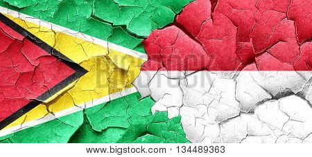 Guyana flag with Indonesia flag on a grunge cracked wall