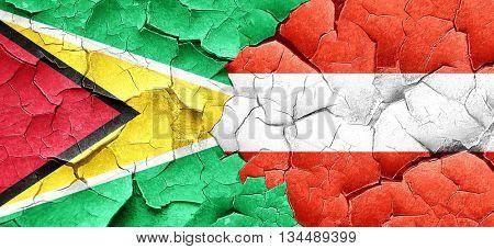 Guyana flag with Austria flag on a grunge cracked wall