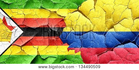 Zimbabwe flag with Colombia flag on a grunge cracked wall
