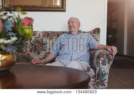 Portrait of a relaxed senior man sitting on a sofa at old age home looking away and smiling
