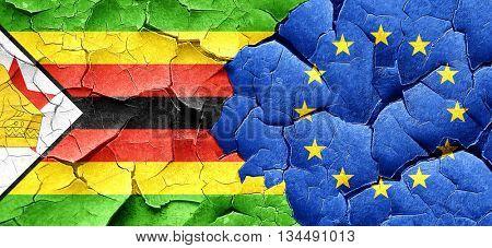 Zimbabwe flag with european union flag on a grunge cracked wall