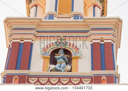 Chettinad India - October 17 2013: Chidambara Palace in Kadiapatti. Krishna statue on top of facade. He sits on bull and plays the flute. Niche and towers.