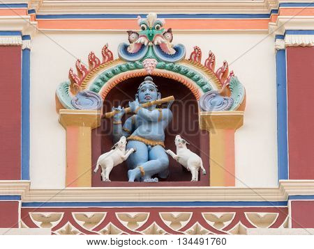 Chettinad India - October 17 2013: Chidambara Palace in Kadiapatti. Blue Krishna playing flute and dancing goats statue on front facade. Set in framed niche.
