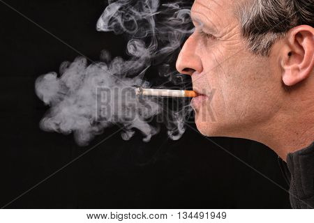 Side view of young man is smoking cigarette on black background.