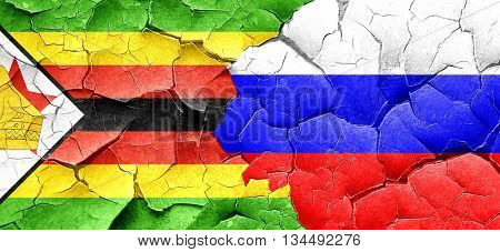 Zimbabwe flag with Russia flag on a grunge cracked wall