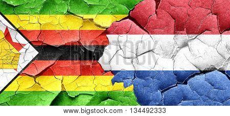 Zimbabwe flag with Netherlands flag on a grunge cracked wall