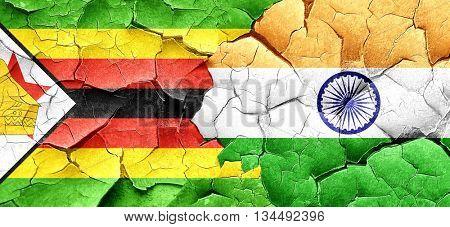 Zimbabwe flag with India flag on a grunge cracked wall
